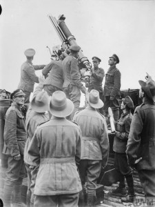 Australian troops watching British soldiers manning an anti-aircraft gun at Morbecque