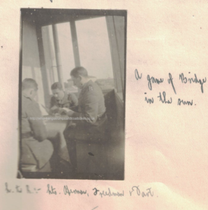 On the veranda at Solombola A game of Bridge in the sun. Left to right Lieutenants Herman, Freedman and Dart.